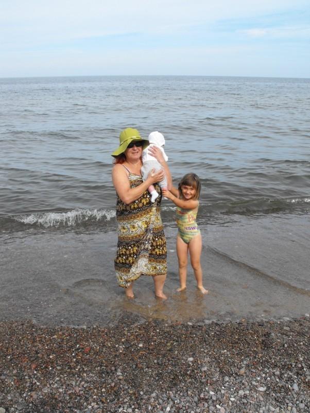 Babcia Tania z wnukami nad morzem. Zwiewna suknia, fantazyjny kapelusz i uśmiech na twarzy. Zew natury. Zew smaku wolności i bezkresu.
