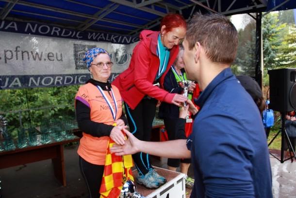 Na pomarańczowo Maria Zawadzka. Robert Brzeziński - organizator Pucharu Polski Nordic Walking - wręcza jej medal.